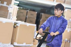 Chinese warehouse worker with forklift stacker Royalty Free Stock Photos