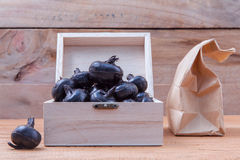 Chinese water chestnut ,water nut or Matai roots in wooden box a. Nd paper bag on rustic old wooden background stock photo