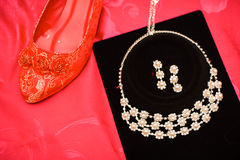 Chinese wedding decoration red shoe and necklace Stock Photos