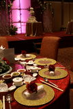 Chinese wedding table setting. Details of a chinese wedding banquet table setting with background of stage and wedding cake Stock Photos