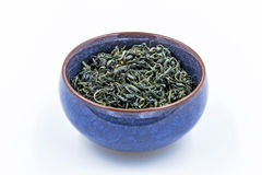 Chinese Wild Green tea. Ye Sheng Lu Cha in a blue ceramic bowl. Isolated on white royalty free stock photos