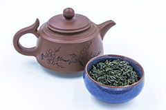 Chinese Wild Green tea. Ye Sheng Lu Cha in a blue ceramic bowl. With small clay pot isolated on white Stock Images