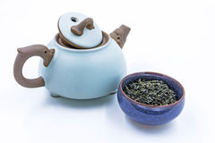 Chinese Wild Green tea. Ye Sheng Lu Cha in a blue ceramic bowl. With small clay pot isolated on white Royalty Free Stock Photography