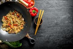 Chinese wok. Asian rice with beef in a wok pan. On black rustic background royalty free stock photography