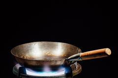 Chinese wok pan on fire gas burner Royalty Free Stock Image