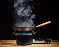 Chinese wok pan on fire gas burner Stock Photo