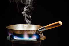 Chinese wok pan on fire gas burner. With smoke, closeup view stock image