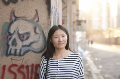 Chinese woman against urban art wall. A chinese woman wearing a black and white striped shirt against a graffiti covered on Moganshan Road in Shanghai China royalty free stock image