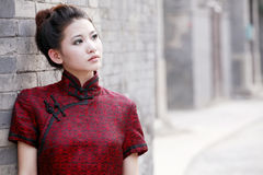 Chinese woman in the alley. Traditional Chinese woman in cheongsam standing in the ancient alley royalty free stock photos