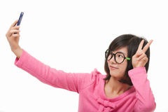 Asian woman using a cell phone to take a selfie isolated on white background Royalty Free Stock Image