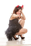 Chinese woman in black dress and devil horns squatting down poin Royalty Free Stock Photo