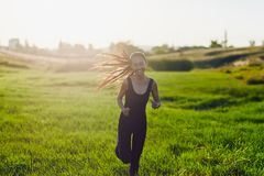 Chinese woman in black sports overalls runs camera in sunshine. Young girl runs to meet in the sun and smiles, enjoys life, rejoices. Image with lens flare Royalty Free Stock Image
