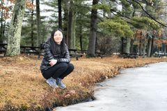Chinese woman Burr Pond State Park. A chinese woman squatting down on the shore of Burr Pond State park in wintertime in Torrington, Connecticut royalty free stock photography