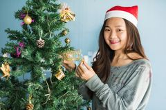 Chinese woman celebrate 2018 Christmas holiday. Happy Chinese woman with Santa Claus hat celebrate Christmas by holding gold Merry Xmas plate on tree to enjoy Stock Photos