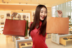 Chinese woman in cheongsam dress carrying shopping bag Stock Image