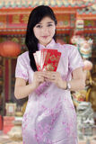 Chinese woman in cheongsam dress giving envelope Stock Photo