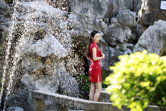 Chinese woman in cheongsam by a fountain in Mudu ancient town Stock Images