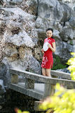 Chinese woman in cheongsam by a fountain in Mudu ancient town Stock Photography