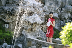 Chinese woman in cheongsam by a fountain in Mudu ancient town Royalty Free Stock Photos