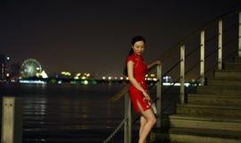 Chinese woman in cheongsam by Jinji lake. ,at beautiful cool night, she carry circular fan; moon-shaped fan; round silk fan on her hand.long black hair royalty free stock photography