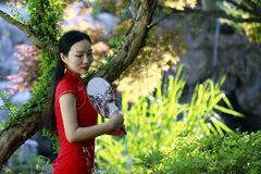 Chinese woman in cheongsam by a lake in Mudu ancient town Stock Photo