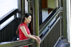 Chinese woman in cheongsam stand in wooden stairs in Mudu ancient town Royalty Free Stock Images