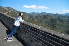 A Chinese woman on China Badaling Great Wall. Sit on China Badaling Great Wall, long hair, blue jeans, black casual shoes. stand by a part of the wall royalty free stock image