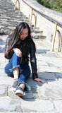 A Chinese woman on China Badaling Great Wall. Sit on China Badaling Great Wall, long hair, blue jeans, black casual  shoes Stock Images