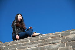 A Chinese woman on China Badaling Great Wall. Sit on China Badaling Great Wall, long hair, blue jeans, black casual  shoes Royalty Free Stock Image