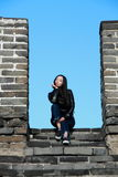 A Chinese woman on China Badaling Great Wall. Sit on China Badaling Great Wall, long hair, blue jeans, black casual  shoes Stock Photos