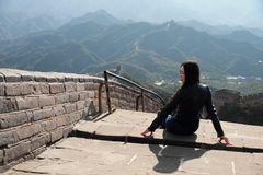 A Chinese woman on China Badaling Great Wall. Sit on China Badaling Great Wall, long hair, blue jeans, black casual  shoes Royalty Free Stock Images