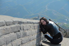 A Chinese woman on China Badaling Great Wall. Sit on China Badaling Great Wall, long hair, blue jeans, black casual  shoes. mountain behind Stock Image
