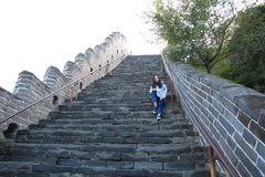 A Chinese woman on China Badaling Great Wall. Sit on China Badaling Great Wall, long hair, blue jeans, black casual  shoes. sit on the middle of the long Royalty Free Stock Photo