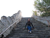 A Chinese woman on China Badaling Great Wall. Sit on China Badaling Great Wall, long hair, blue jeans, black casual  shoes. sit on the middle of the long Stock Image