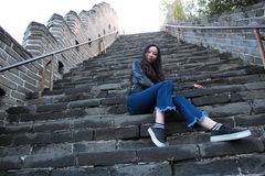 A Chinese woman on China Badaling Great Wall. Sit on China Badaling Great Wall, long hair, blue jeans, black casual  shoes. sit on the middle of the long Royalty Free Stock Image