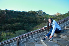 A Chinese woman on China Badaling Great Wall. Sit on China Badaling Great Wall, long hair, blue jeans, black casual  shoes. sit on the long stone stairs Stock Photos