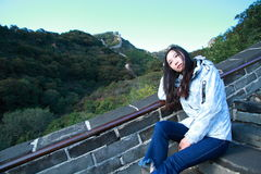 A Chinese woman on China Badaling Great Wall. Sit on China Badaling Great Wall, long hair, blue jeans, black casual  shoes. sit on the long stone stairs Royalty Free Stock Images