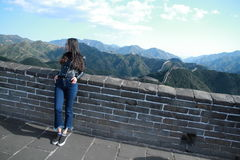 A Chinese woman on China Badaling Great Wall. Sit on China Badaling Great Wall, long hair, blue jeans, black casual  shoes. stand on the Great wall Stock Photography