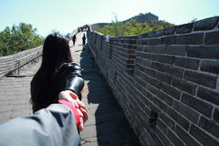 A Chinese woman on China Badaling Great Wall. Sit on China Badaling Great Wall, long hair, wear leather clothing,blue jeans, black casual shoes. hand royalty free stock image