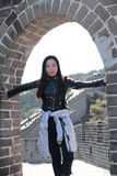 A Chinese woman on China Badaling Great Wall. Sit on China Badaling Great Wall, long hair, wear leather clothing,blue jeans, black casual shoes royalty free stock images