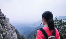 Chinese woman looking out over songshan. A chinese woman on the cliff walk at Mount Song songshan overlooking the sheer cliffs in Henan Province China Dengfeng royalty free stock photo