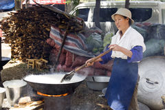 Chinese Woman Cooking Rice. A Chinese woman stirs rice in a wok at the Third Month Fair, a 5,000 year old fair in Dali, Yunnan province, China Stock Image