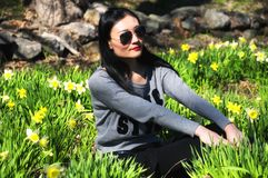 Chinese woman in daffodil Park. A chinese woman sitting in a field of daffodils wearing sunglasses in the springtime of New England at Laurel Ridge Daffodil Park royalty free stock image