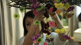 Chinese woman decorates interior of room with floral garlands. stock footage