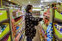 A Chinese woman is delighted to find her favorite biscuits. Shenzhen royalty free stock photos