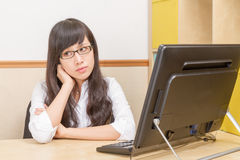 Chinese woman at desk daydreaming Royalty Free Stock Photos