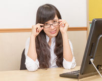 Chinese woman at desk holding glasses Royalty Free Stock Photos