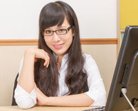 Chinese woman at desk looking happy Royalty Free Stock Photos