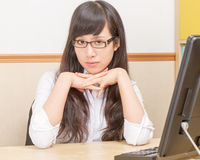 Chinese woman at office desk looking serious Stock Image