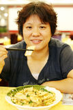 Chinese woman dining. Chinese middle-aged woman is having the dinner in a Chinese restaurant Royalty Free Stock Images